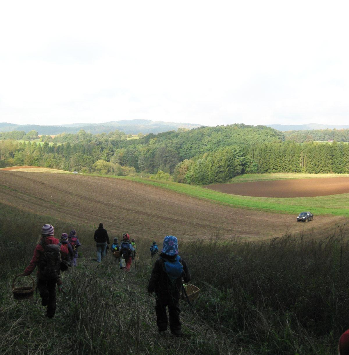 Waldkindergarten-Merzig-Besseringen Von einem Hügel aus geht es tief ein Tal mit vielen Feldern. Am Horizont ist der Wald zu sehen. Einige Kindern rennen oder gehen den Hügel zum Tal hinunter.